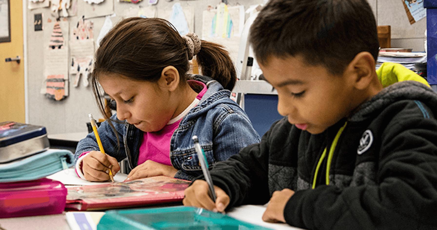 Students writing at desk